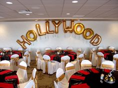 DIY Hollywood Theme: Buy Large Individual Letter Balloons attach curly ribbon at ends...white chair cover, gold sashes, black overlays & red napkins!