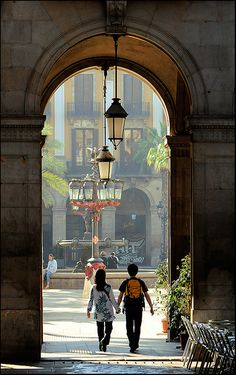 Strolling under the arches of Plaça Reial in Barcelona, Spain (by S. Lo).