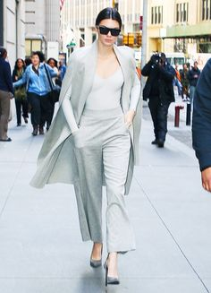 Kendall Jenner wears a gray bodysuit, cape, gray trousers, and gray suede heels
