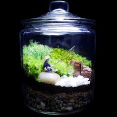Japanese garden terrarium features a fisherman relaxing atop his river rock with a tiny white fish on his line with a realistic forest scene in the background. Terrarium features 3 different types of moss: mood, Terrarium Diy, Glass Terrarium, Deco Nature, Deco Floral, Cactus Flower, Flower Bookey, Flower Film, Flower Pots, Flower Fence