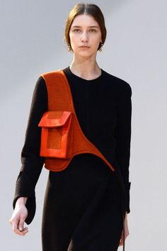 """Phoebe Philo continues to innovate in the accessory arena, this season introducing the holster handbag in an orange shade—the ultimate """"hands-free"""" bag."""