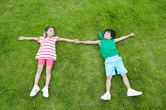 Boy and girl lying on grass, holding hands, view from above Children Holding Hands, Hand Photography, Boy Photos, Still Image, Royalty Free Images, Boy Or Girl, Grass, Stock Photos, Boys