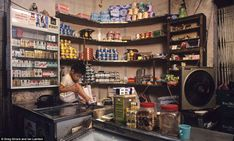 A child with a grazed knee sits on a counter top in a tiny shop which sells essentials like toilet paper and canned foods. Cigarettes are al...