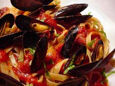 SPICY MUSSELS MARINARA ~ 1 tablespoon olive oil 1 cup finely chopped onion 3 garlic cloves, minced 2 cups chopped tomato 1/2 cup dry white wine 1/3 cup chopped fresh flat-leaf parsley 2 tablespoons chopped fresh basil 1/2 teaspoon salt 1/2 teaspoon black pepper 1/4 teaspoon crushed red pepper 2 bay leaves 5 pounds fresh mussels, scrubbed and debearded (about 100 mussels) 5 cups hot cooked linguine (about 10 ounces uncooked pasta) Basil sprigs (optional)