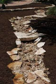 """One family's xeric project - """"We"""" dug an 80' dry creek bed which has three """"bridges"""" across it. (Sula Howell)"""