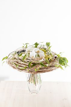 Handtied bouquet by Slava Rosca, with white orchids, trailing vine and a natural, woven collar.