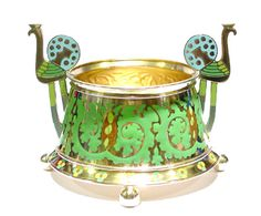 A champleve and cloisonné enamelled silver gilt bratina by Carl Fabergé,  gilded silver, of tapering circular form decorated with undulating swirls of champleve green enamel foliage and stylised cloisonn� enamelled green and brown cones, the flared base enamelled with champleve quatrefoil flowers, supported on four ball feet, the handles enamelled in the form of peacocks.  Moscow, circa 1905, inventory number: 18925. 84 zolotniks