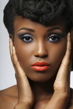 1970's or 80's style makeup. Brown skin and tangerine lips, blue eyeliner under and above eye, shaped brows, smooth shiny foundation.