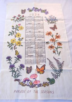 This unused 1974 linen flour sack calendar towel is decorated with the Parade of Seasons, a border of seasonal flowers, insects, mushrooms, and