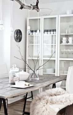 hanging white bulbs on a wooden branch #diy  wooden table with industrial black legs & wool throw to soften.