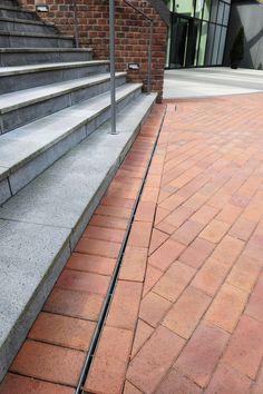 Dränagerinnen und Entwässerungsrinnen der Firma Richard Brink sorgen dafür, dass Niederschlagswasser an den Außenbereichen zuverlässig abgeleitet wird. Die Schlitzrinnen vor den Treppen am Haupteingang dienen der Linienentwässerung