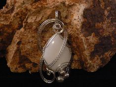 You will be seen across the room wearing this beautiful pendant. The stone is a lovely white agate cut in a tear drop shape and beautifully wire wrapped in Sterling Silver with 3 vintage platinum pearls to set it off. The pendant measures 3x1.5 chain is not included Agate