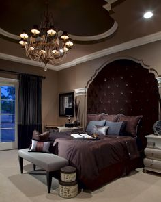 The custom velvet headboard is a stunning focal point in this traditional master bedroom. Rich shades of brown create a soft, relaxing environment, while a stunning gold and crystal chandelier hanging from the coved ceiling brings in an element of glamour.