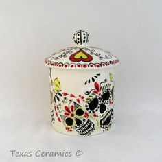 Small Skull Container and Lid with hand painted Mexican Day of the Dead folk art design. This cylinder shape canister is decorated with skulls that