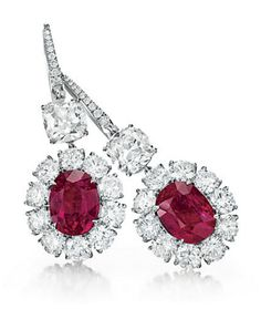 A PAIR OF RUBY AND DIAMOND EAR PENDANTS. Each set with an oval-cut ruby, weighing approximately 5.05 and 4.20 carats, within a circular-cut diamond surround, from an old mine-cut diamond, weighing approximately 2.02 and 2.01 carats, to the circular-cut diamond French wire, mounted in platinum