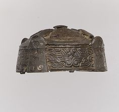 Viking Round Box Brooch; ca 1000-1100, Gotland, Sweden  Worn by women on Gotland to affix their shawls at the collarbone and also held small objects. This brooch is decorated with tiny beasts inhabiting the interlace patterns on the top and sides.   Medium: copper alloy, cast, selectively applied silver foil (OA XRD)