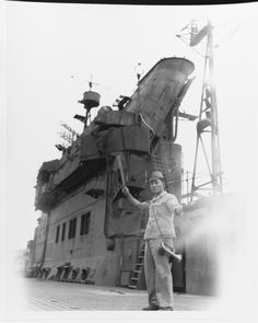 """""""Japanese aircraft carrier Junyo. A member of the ship's residual crew signals an approaching tug from the carrier's flight deck. Taken at Sasebo, Japan, 19 October 1945. Note this Japanese Signalman's bugle, and details of the ship's island."""""""