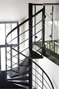 Photo DH111 - Passerelle en acier au design épuré et contemporain pour appartement type loft et escalier hélicoïdal SPIR'DÉCO® Contemporain de notre Gamme Initiale (Standard). Ossature composée de marches Nanoacoustic® espacées pour une passerelle tout métal sans effet de résonance et silencieuse. Garde-corps avec panneau verre sécurit feuilleté fixé par pinces aux montants. Escalier d'intérieur métallique hélicoïdal design. Finition : acier brut patinée. - © Photo : Nicolas GRANDMAISON