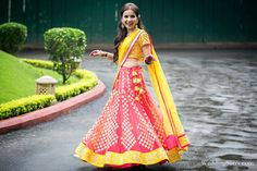 A coral & yellow lehenga choli by Amrita Thakur for the mehendi of Rashmi Bajpai of WeddingSutra.