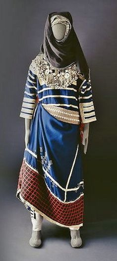 A costume of the Thaqeef tribe from the Hada area (Saudi Arabia). The yoke and arm bands are embroidered with gold thread. The small white decorative motif above the hem is tie-dyed. The accompanying belt is made with metal beads and sea shells.  (Source: Mansoojat Foundation).