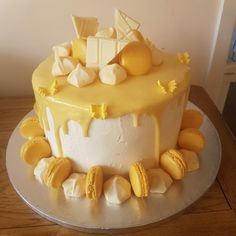 Lemon and white chocolate drip cake with macarons and meringues. Www.cookcakes.co.uk