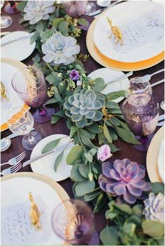 Greenery table runner wedding inspo: eucalyptus with silver and purple succulents. Gold and white dishes and a purple tablecloth complete the look.