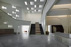 A wide staircase fitted with seating is placed at the centre of the lobby. It leads up to the first floor, towards exhibition rooms and breakout spaces beside a wall of the asymmetrically scattered windows.