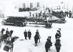 Een stuk Bofors 10 cm veldgeschut achter een Trado artillerietrekker passeert tijdens een defilé een in een tuin opgesteld muziekkorps en een aantal te paard gezeten militairen.