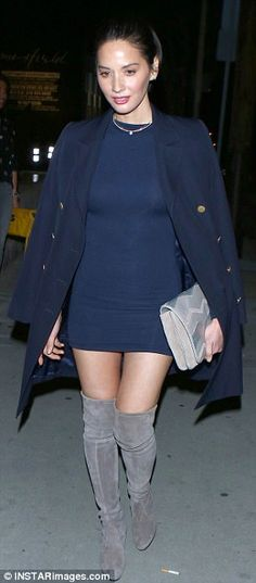Layers: A matching coat was draped over her shoulders, while she carried a grey textured clutch bag