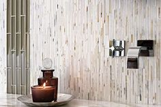 Rectangular tiles in mixed neutrals, stacked vertically up a bathroom wall, create an interesting rippling effect that's easy on the eyes and make the bathroom appear larger. Shown: Heavy Rain Mosaic, Calacatta, AKDO