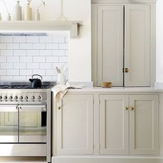 Kitchen— putty-colored cabinets, white subway tile and brass hardware