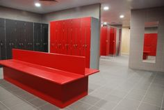 Solid surface changing bench, and red and black/grey lockers.