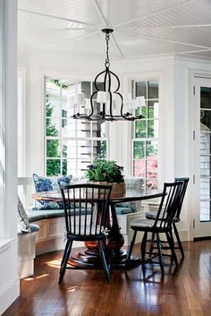 Built-in bay window seat with round table and black chairs