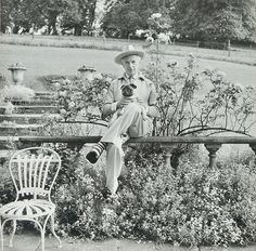 Cecil Beaton, c. 1960s, seated on terrace balustrade at Reddish House, Broad Chalke, with his Pug. By Ida Kar?