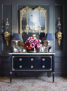 Layering shades of deepest, darkest grey blue, totally over the top gilt mirror with double pagoda detailing, glossy navy-black chest on legs with gold detailing and marble top, and a fab leopard print carpet tying it all together. By Larry Hooke Interiors in Seattle