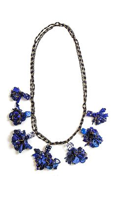 Robin Ayres – This necklace started as seven blue dice. Now each dice holds a tassle of vintage beads, Cracker Jack pieces, game pieces, and much more
