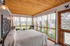 In the Pacific Northwest, this eclectic-rustic-style sleeping porch enjoys views of the surrounding organic farm and mountains. In spring, b...