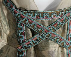 Neckline, skirt, and train all edged with bands of blue green and orange pink beads.
