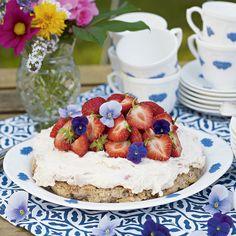 Mandelkaka toppad med rabarbergrädde och jordgubbar blir en ljuvlig sommardessert.