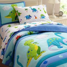 """Create a charming """"""""land before time"""""""" for a little boy's bedroom with the Dinosaur Land Comforter and Bedding Collection from Olive Kids. Brightly colored, playful dinosaurs are displayed on a white"""