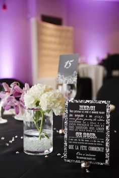 Modern black and white reception table stationery and hurricane vases with floral centerpieces
