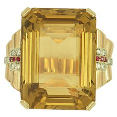 Large Scale Retro Period Citrine Ring. One mid-century, ladies 14K rose gold ring set with an enormous emerald cut citrine weighing approximately 87ct. This large center stone is accented by beautifully scrolled shoulders, set with approximately 0.15ct of round brilliant cut diamonds, and approximately 0.15ct of rubies. c 1950