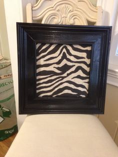 Black frame with Zebra print burlap over cork board to pin pictures.