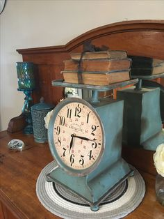 Turquoise clock scales on top of antique sideboard