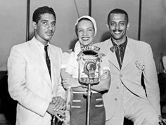Dorival Caymmi, Carmen Miranda e Assis Valente posam com o microfone da Radio Mayrink Veiga (esq-dir). O jovem compositor despontava, mas vivia uma vida de dívidas e angustias, suicidando-se em 1958 (Reprodução)
