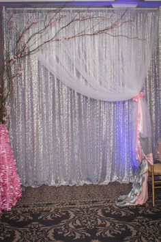 A stunning all sequin Silver Backdrop with the softness of white sheer organza and curly willow accenting the look. By True elegance Design & Decorating.