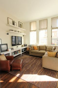 How to Keep a TV from Standing Out Like a Sore Thumb - Create lines around it  The shelves above this tv both draw the eye upward and above it, but also create horizontal lines on the wall and the tv becomes just more horizontal lines.