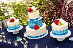 spanish tile wedding cake in center, lace trimmed bottom tier, and paper flag pattern on top layer