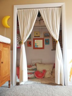i love the curtains and the children's artwork on the wall :) Kids Closets Used as Reading Nooks