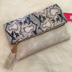 Ivory Python & Tassel Flap Over Clutch Brand new with tags. Beautiful Ivory Python Flap Over Clutch. Includes chain strap. H: 7.0 L: 10.0 W: 2.0 Faux Leather, 2 compartments, and 1 zipper pocket flap over zipper, and magnetic closure. Bags Clutches & Wristlets